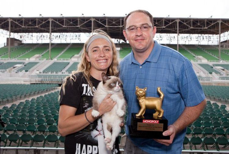 Мужчина и женщина с кошкой и кубком
