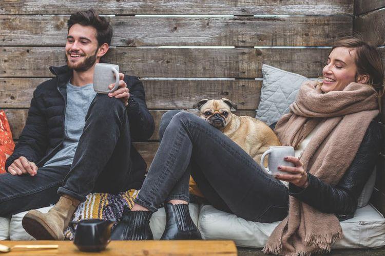 Пара с собакой пьют кофе